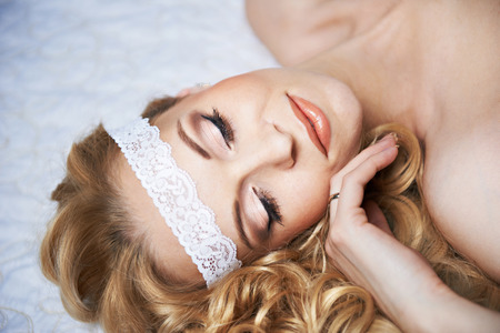 closed eyes: Mooi meisje ligt op wit bed met gesloten ogen