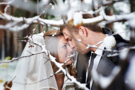 winter couple: Lovers bride and groom look at each other in winter day