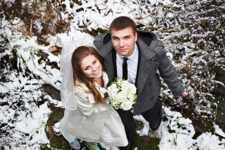 Happy bride and groom in winter day on their wedding photo