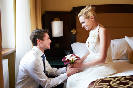 Happy bride and groom in bedroom on wedding day photo
