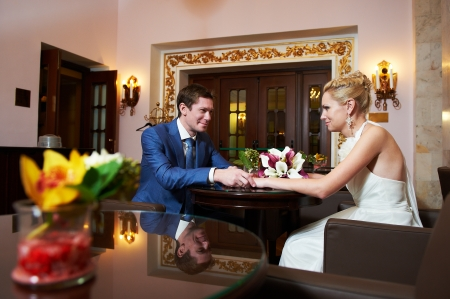 Happy bride and groom in interior of hotel in wedding day photo