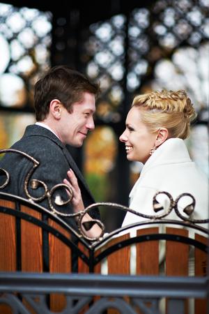 Happy bride and groom on decorative bench at wedding walk photo