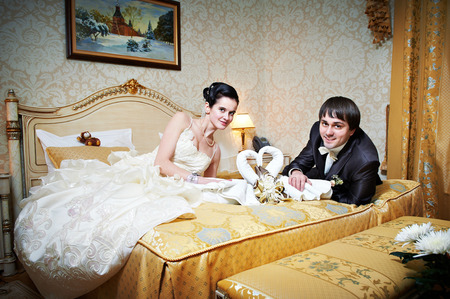 Handsome bride and groom in bedroom on wedding day photo