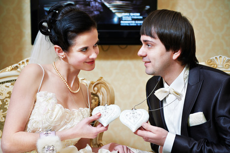 Bride and groom with heart-shaped mascots indoors photo