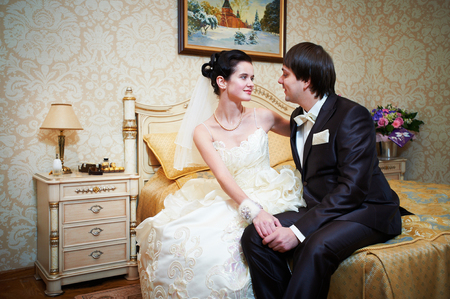 Handsome bride and groom in bedroom on wedding day Stock Photo - 24209880