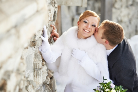 Romantic kiss happy bride and groom on winter wedding day Standard-Bild