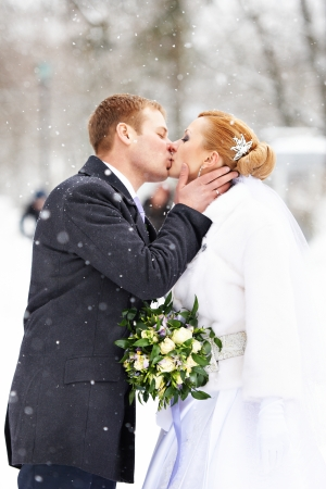 a marriage meeting: Romantic kiss happy bride and groom on winter wedding day Stock Photo