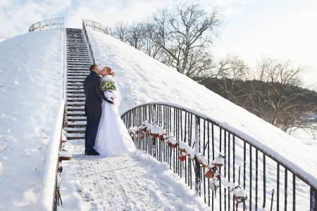 Romantic kiss happy bride and groom on winter wedding day Stock Photo