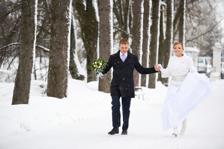 Happy bride and groom running in winter park on wedding day photo