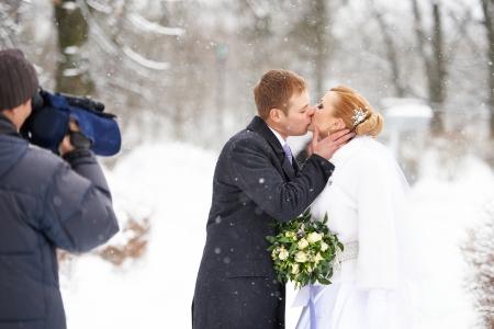 Operator shooting romantic kiss happy bride and groom on winter wedding day