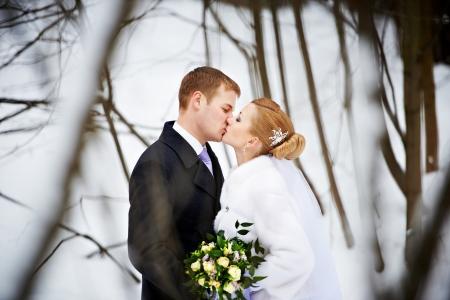 parejas de amor: Beso de la novia y el novio en el bosque de invierno