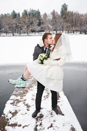 carries: Bride and groom walking in winter in wedding day
