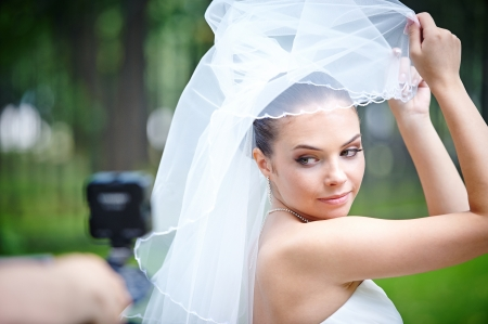 Beautiful bride posing for videographer in wedding day Фото со стока
