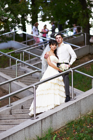 Bride and groom on stairs in park photo