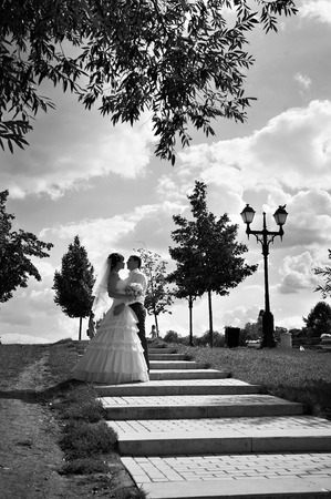 Bride and groom in park on stairs photo