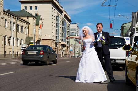 Funny bride and groom catch a taxi on the street in wedding day photo