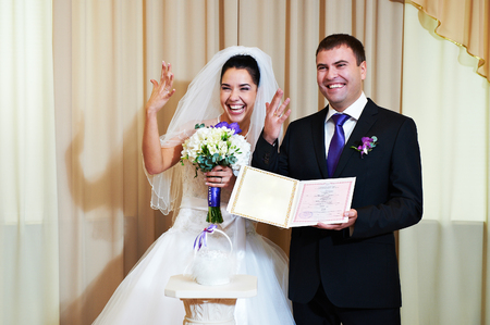 marriage certificate: Bride and groom showing their wedding rings and marriage certificate