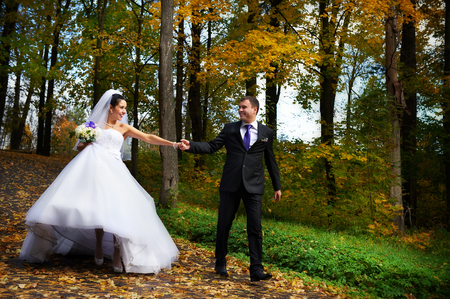 Happy bride and groom walking in yellow autumn park