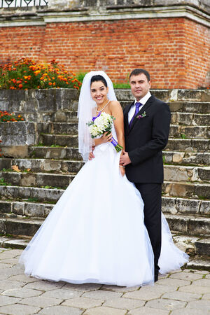 Happy bride and groom near ancient ladder at wedding walk photo