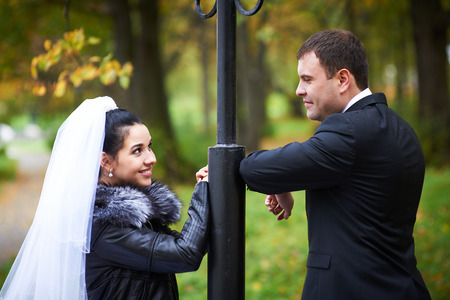 Happy bride and groom in autumn park on wedding walk photo