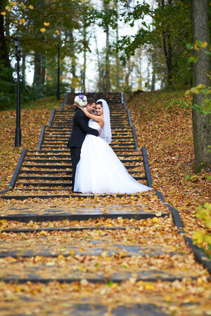 Happy bride and groom in yellow autumn foliage on wedding walk photo