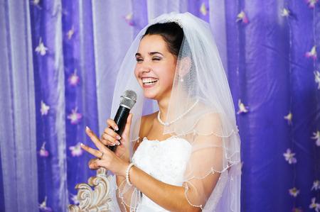 Joyful bride speaks at banquet on her wedding Фото со стока