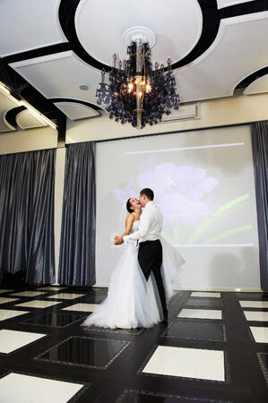 Dance bride and groom in banqueting hall on them wedding photo