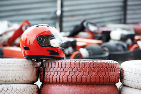 Red helmet with visor is on tires by kartodrom