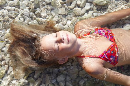 little blonde girl: Little girls on beach of sea at summer