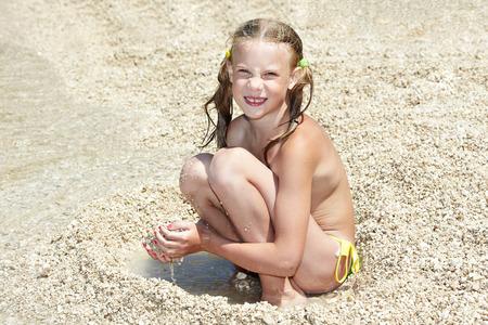 sitting ground: Little girls on beach of sea at summer