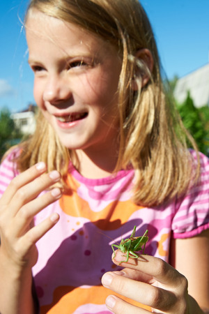Girl with a grasshopper on a hand photo