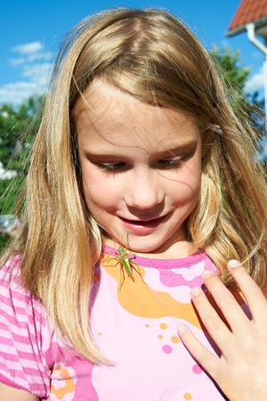 Grasshopper crawling across the face of a happy girl photo