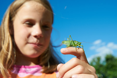 Girl with a grasshopper on a hand in summer photo