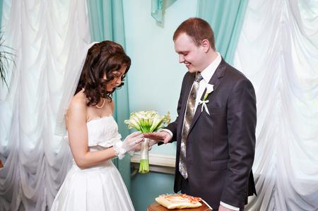 solemn: Happy bride wears wedding ring her groom. Solemn registration of marriage. Stock Photo
