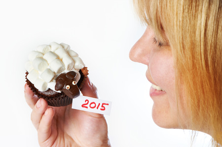 Young woman holds cake lamb as simbol 2015 new years isolated on white background photo