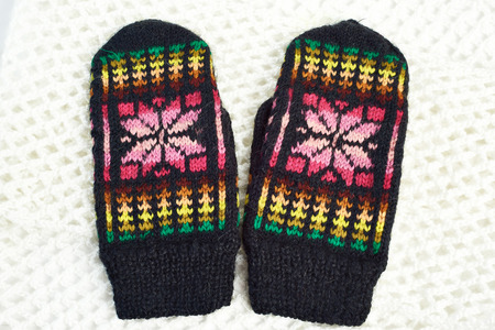 Knitted mittens on a background of white scarf photo