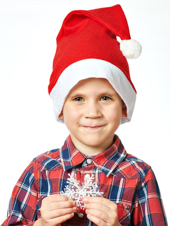 blithe: Little boy in red Santa hat and snowflake in his hand
