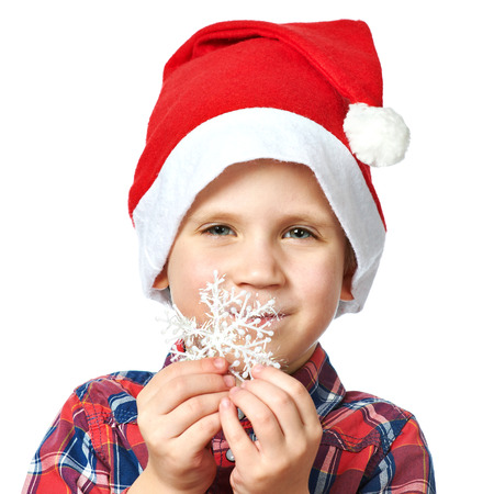 Little boy in red Santa hat and snowflake in his hand photo