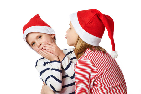 Girl and little boy in Santa Claus hat on white background photo