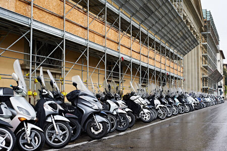 mopeds: A lot of mopeds on the city street in rainy weather Stock Photo