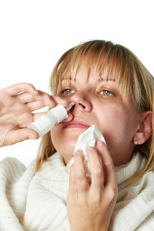nasal drops: Sick with a rhinitis woman dripping nose medicine isolated on white Stock Photo
