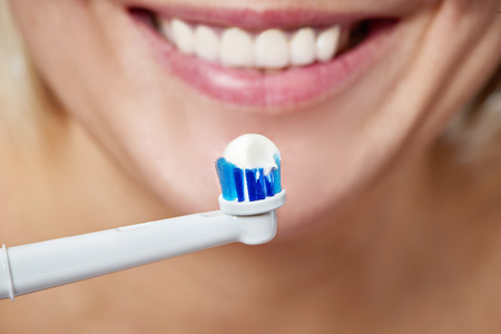 Woman brushing teeth electric toothbrush with toothpaste closeup