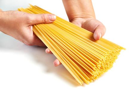 Hand holding spaghetti isolated on white background photo