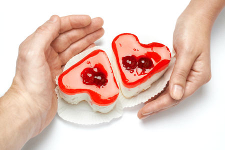 Jelly heart-shaped cakes in hands of lovers on white background photo