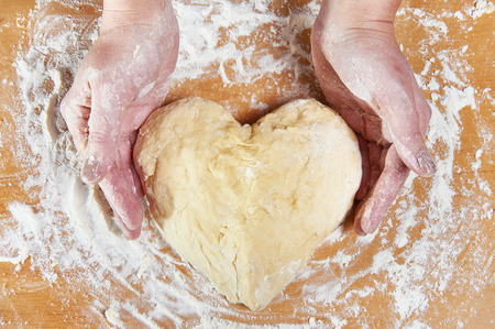Woman holding dough heart in his hands photo