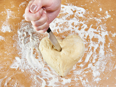 struck: Hand with knife struck the heart of the dough