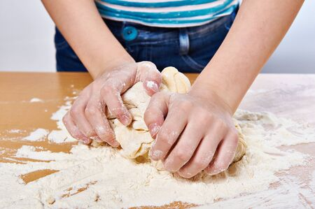 kneading: Kneading dough on girl hands close-up Stock Photo