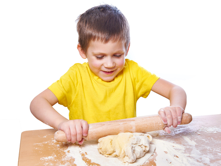 Happy boy kneads and rolling dough for pie on kitchen table isolated photo