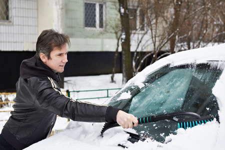 Driver with a brush cleans the car from the snow in the winter photo