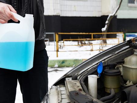 antifreeze: Male driver fills antifreeze liquid in the washer window